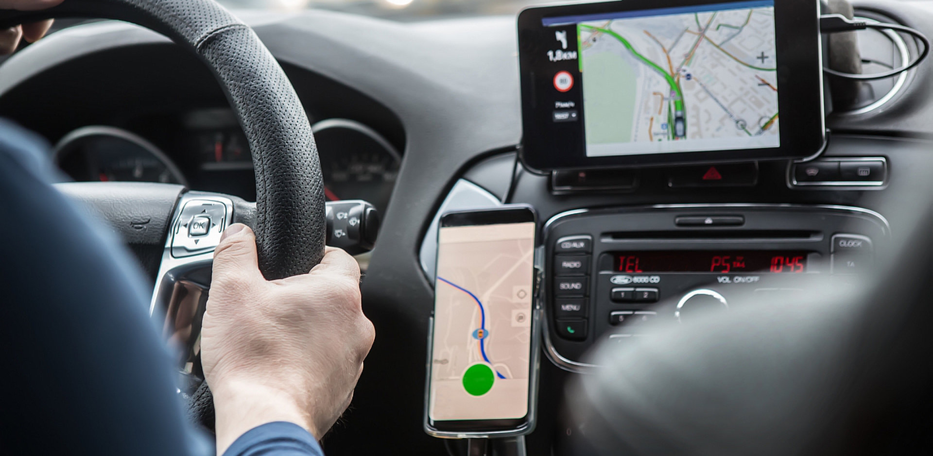 driver driving his car with a map on his phone